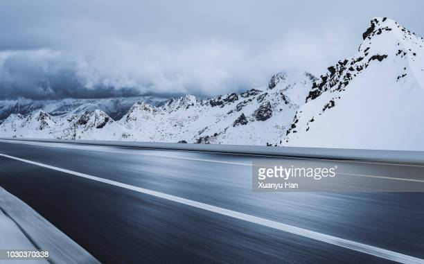 empty road leading to snow covered mountains - two lane highway stock pictures, royalty-free photos & images