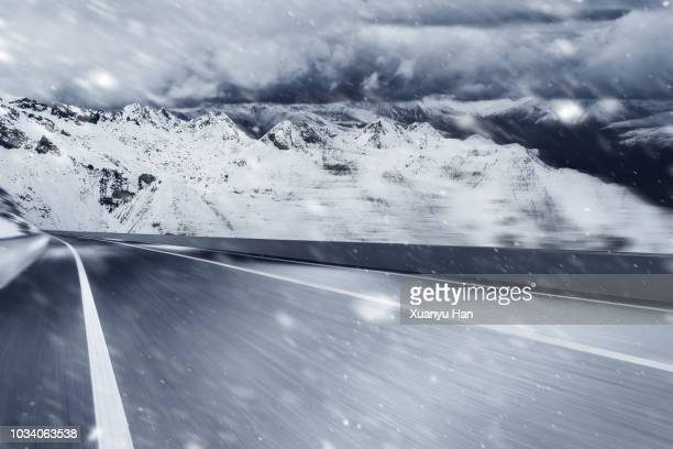 empty road leading to snow covered mountains - 雪 ストックフォトと画像