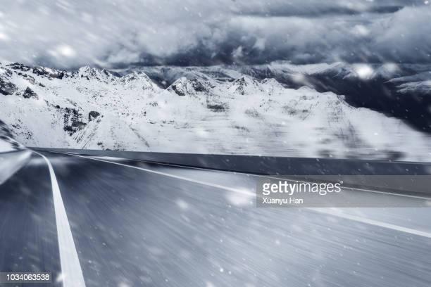 empty road leading to snow covered mountains - snow storm - fotografias e filmes do acervo