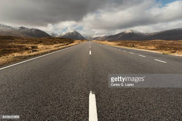 Empty road leading to snowy mountains in the Glen Coe Valley