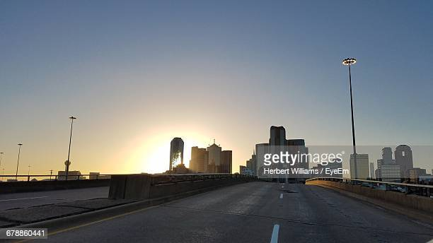 Empty Road Leading Towards Buildings In City Against Sky During Sunset
