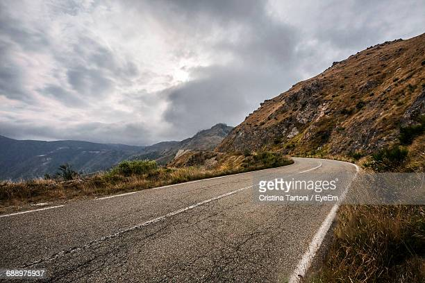 empty road leading towards mountains against cloudy sky - mountain road stock pictures, royalty-free photos & images