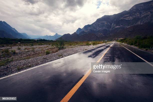 empty road leading towards mountains against cloudy sky - nass stock-fotos und bilder