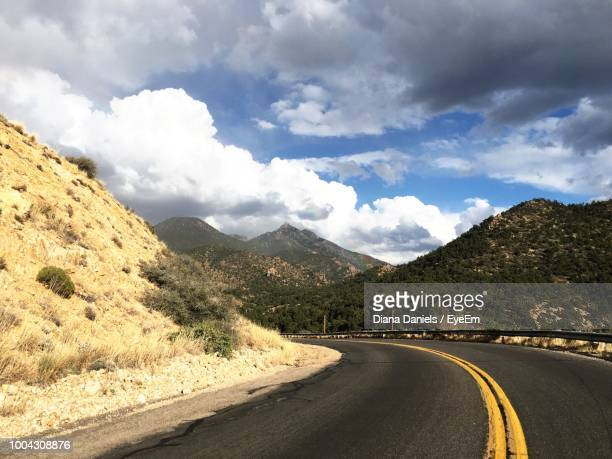 empty road leading towards mountains against sky - diana daniels stock-fotos und bilder