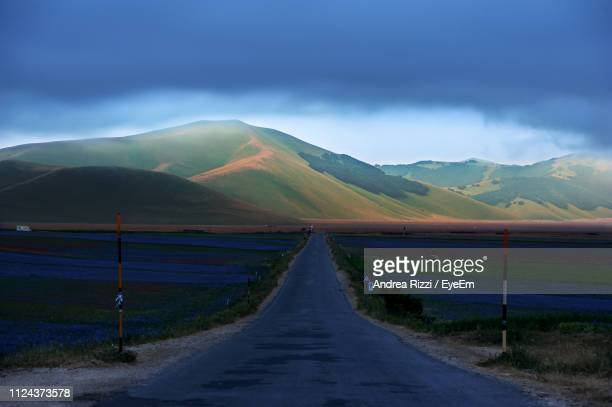 empty road leading towards mountains against sky - andrea rizzi stockfoto's en -beelden