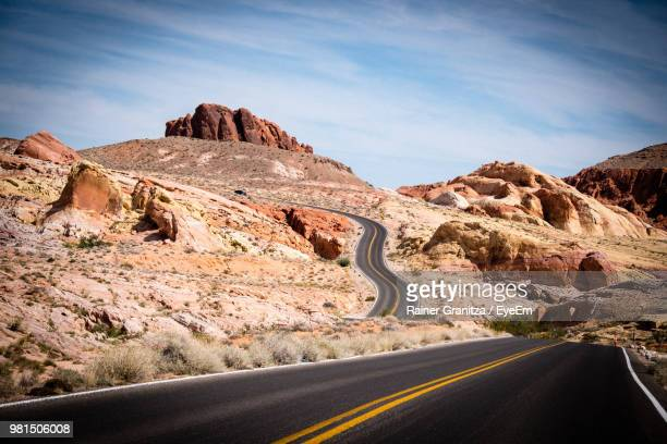 empty road leading towards mountains against sky - valley of fire state park stock photos and pictures