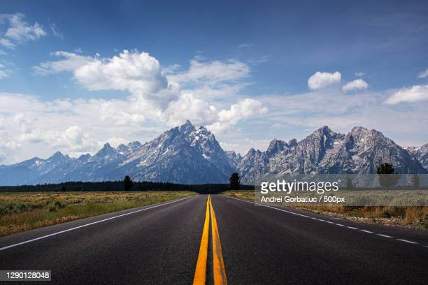 empty road leading towards mountains against sky,grand teton,wyoming,united states,usa - ティトン山脈 ストックフォトと画像