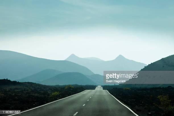 empty road leading towards mountains in lanzarote, canary islands, spain - direction imagens e fotografias de stock
