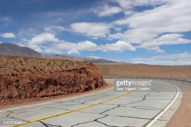 empty road leading towards mountains - salta argentina stock photos and pictures