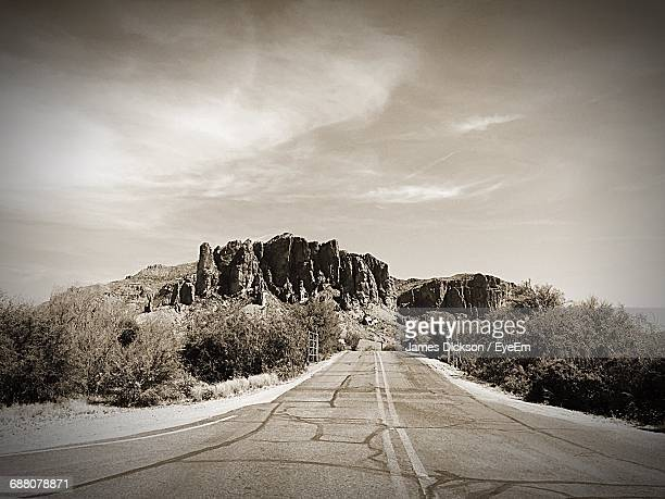 Empty Road Leading Towards Rock Formation Against Sky