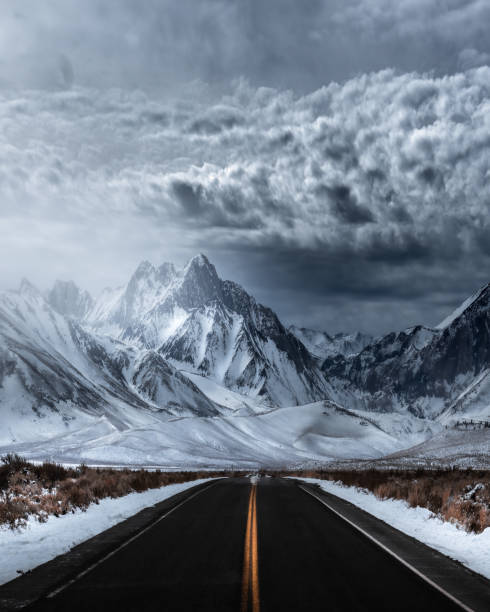 Empty road leading towards snowcapped mountains against sky,Mammoth Lakes,California,United States,USA