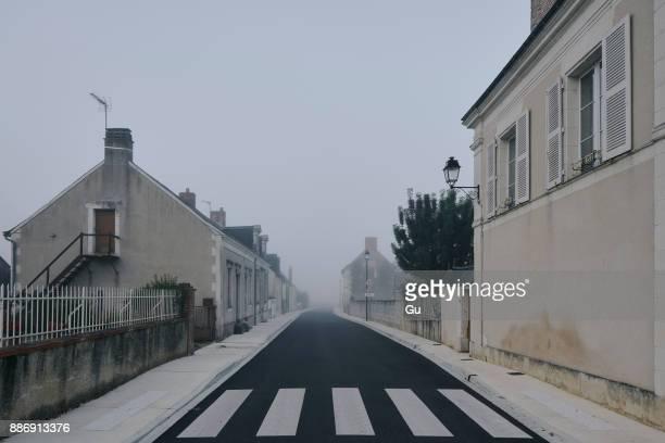 empty road through meigne-le-vicomte village on misty morning, loire valley, france - freie straße stock-fotos und bilder