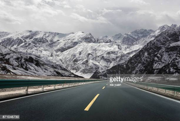 Empty road through snow mountains