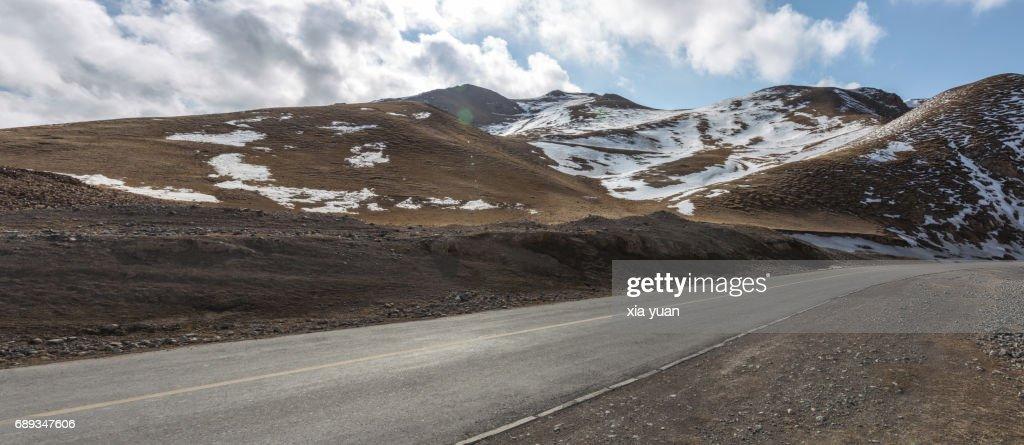 Empty road through snowcapped mountain : Stock Photo