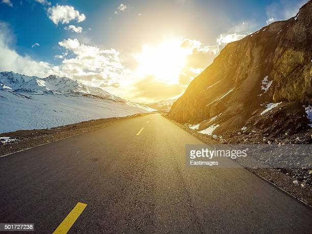 Empty road through snowy mountains in sunshine.