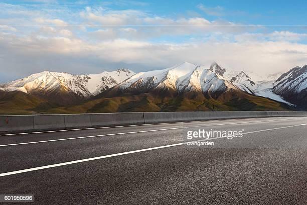 Empty road through snowy mountains