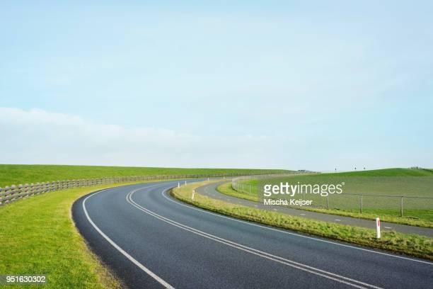 empty road through the dyke besides the waddense, holwerd, friesland, netherlands - 干拓地 ストックフォトと画像