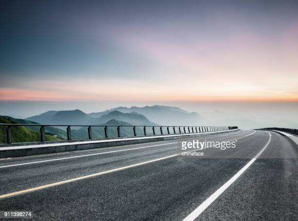 empty road travel through mountain range - empty road stock pictures, royalty-free photos & images
