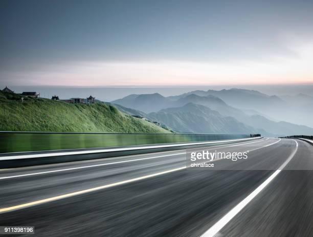 lege weg reis door bergketen, wazig beweging - autosnelweg stockfoto's en -beelden