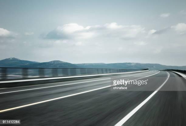 empty road travel through mountain range,blurred motion