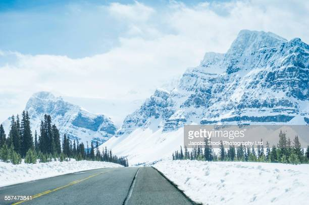 Empty road under snowy mountains