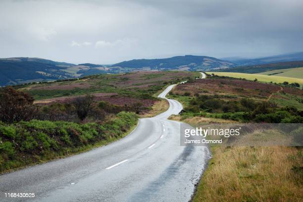 empty road winding across moorland. - road stock pictures, royalty-free photos & images