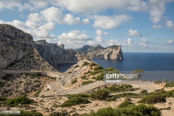empty road winding along edge of cap de formentor headland - majorca stock pictures, royalty-free photos & images