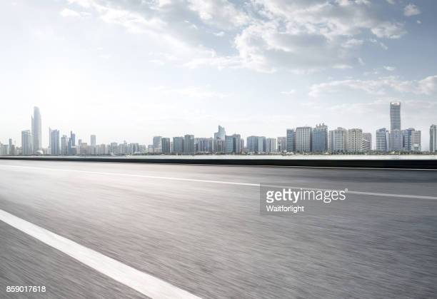 empty road with abu dhabi skyline - urban road stock pictures, royalty-free photos & images
