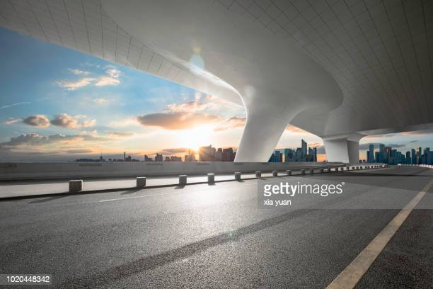 empty road with city skyline - boog architectonisch element stockfoto's en -beelden