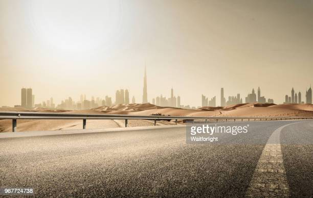 empty road with dubai skyline background - road stock pictures, royalty-free photos & images