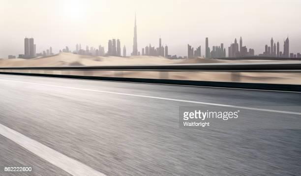 empty road with dubai urban skyline - golfstaaten stock-fotos und bilder