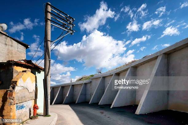 empty road with electric post and support wall . - emreturanphoto stock-fotos und bilder