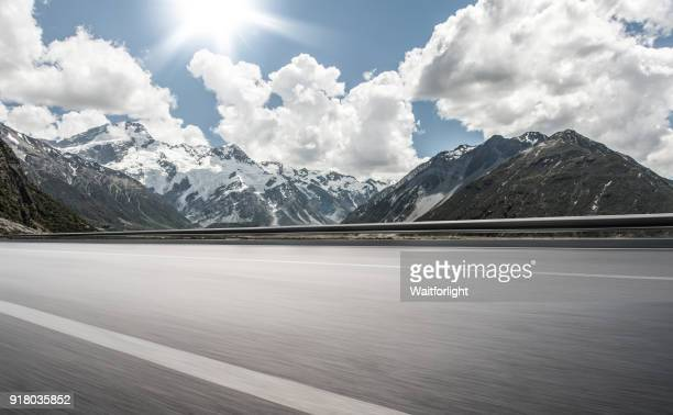 Empty road with snowcapped mountain background