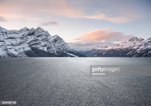 empty road with snowcapped mountain background - asfalto fotografías e imágenes de stock