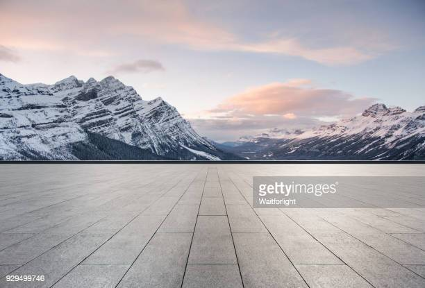 empty road with snowcapped mountain background - sneeuwkap stockfoto's en -beelden