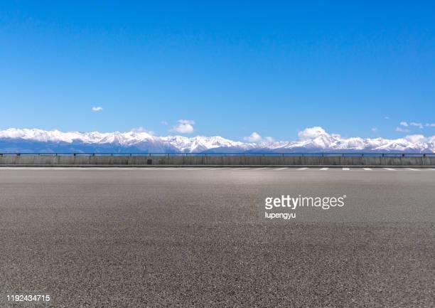 empty road with sonw mountain - vista laterale foto e immagini stock