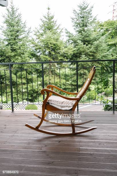 empty rocking chair in porch against trees - rocking chair stock pictures, royalty-free photos & images