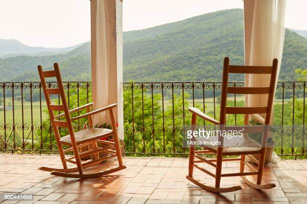 empty rocking chairs in balcony against mountains - rocker stock photos and pictures