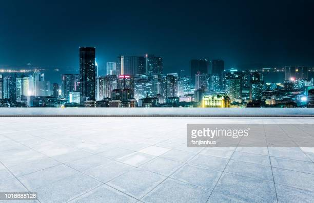 empty rooftop platform front of qingdao cityscape - cityscape stock pictures, royalty-free photos & images