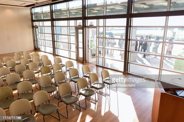 empty room filled with chairs before conference event - town hall stock pictures, royalty-free photos & images