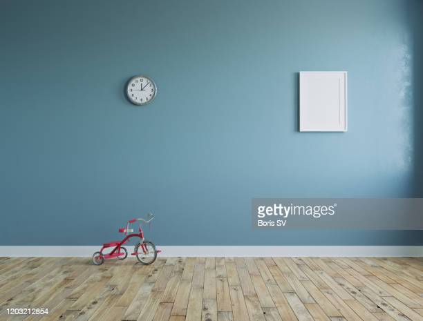 empty room with kid's tricycle and clock on the wall - beige stock pictures, royalty-free photos & images