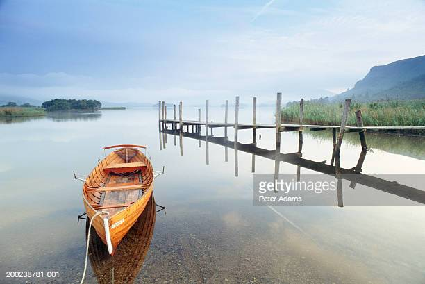 empty rowing boat by wooden jetty on still lake - ponton photos et images de collection