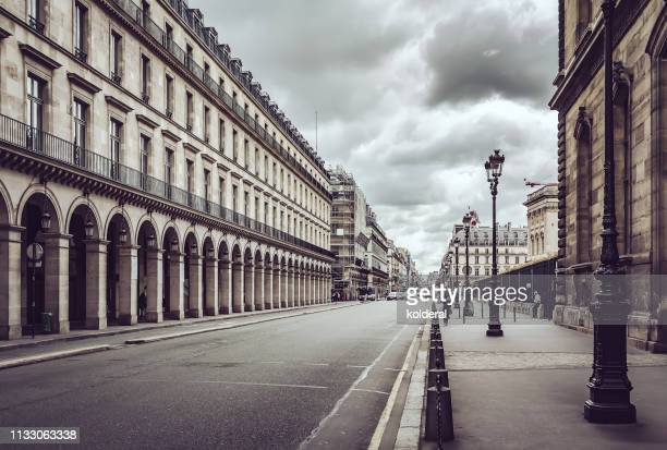 empty rue de rivoli street against dramatic sky in paris - parís fotografías e imágenes de stock