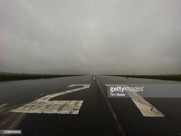 empty runway 27 left at tempelhof airport in berlin on a rainy day. - berlin airlift stock pictures, royalty-free photos & images