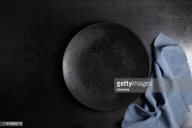 empty rustic black concrete plate and linen napkin - plato vajilla fotografías e imágenes de stock