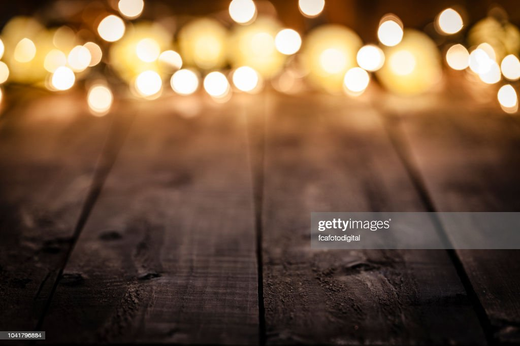 Empty rustic wooden table with blurred Christmas lights at background : Stock Photo