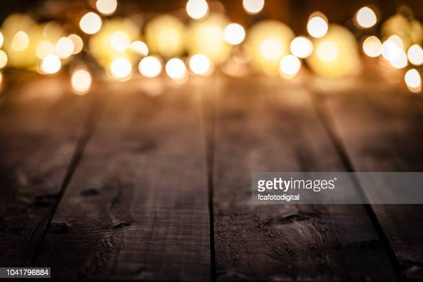 empty rustic wooden table with blurred christmas lights at background - wood material stock pictures, royalty-free photos & images