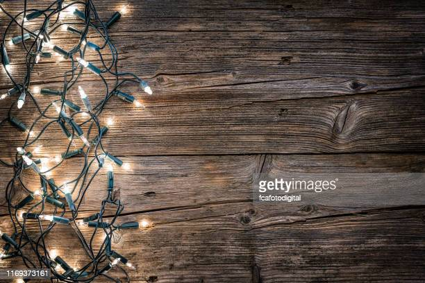 empty rustic wooden table with christmas lights at the bottom border - christmas lights stock pictures, royalty-free photos & images