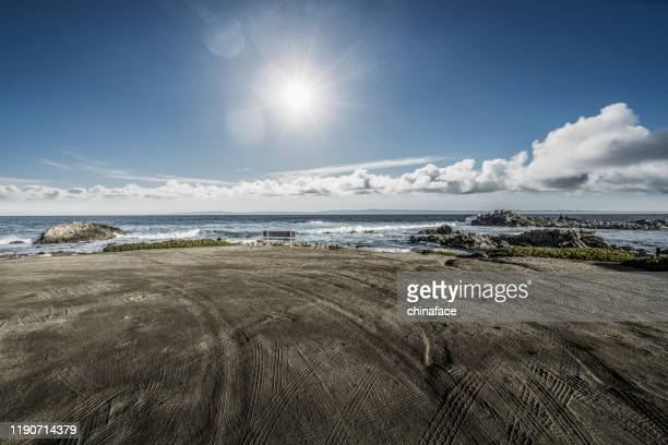 empty sand beach with tyre tracks against sky - dirt road stock pictures, royalty-free photos & images