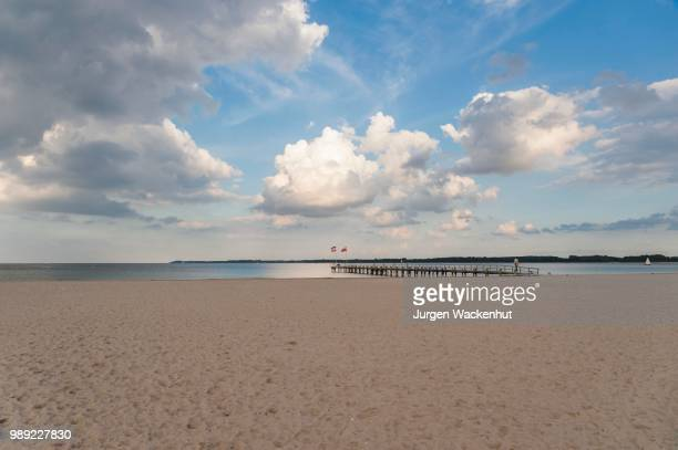 empty sandy beach and pier, cloudy sky, travemuende, baltic sea, schleswig-holstein, germany - schleswig holstein stock pictures, royalty-free photos & images